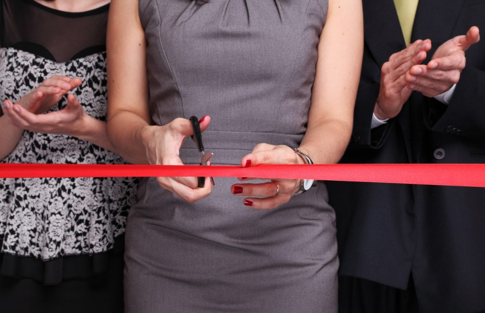 Business woman cutting red ribbon.