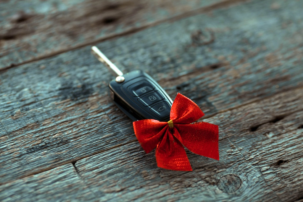 Car key with a red ribbon bow on a wooden background.