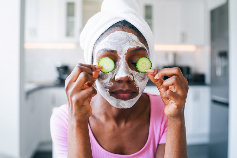 Woman with cucumber on eyes and a facial on her face