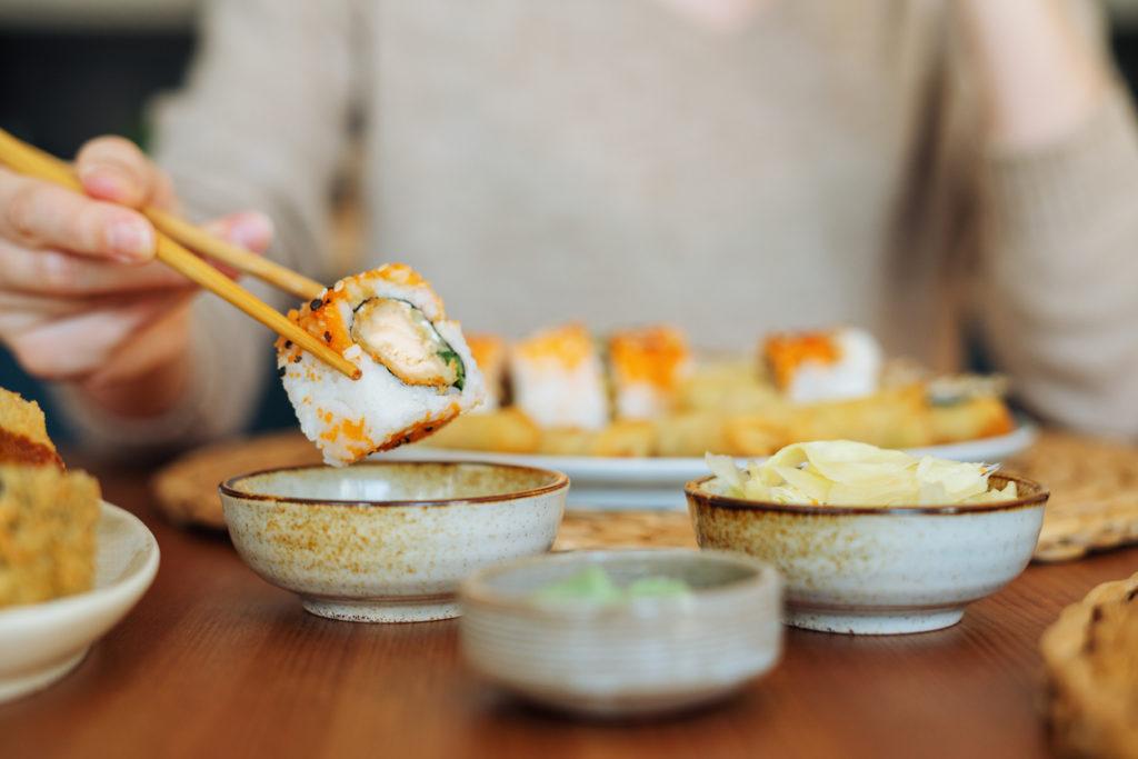 Close up of woman eating maki sushi