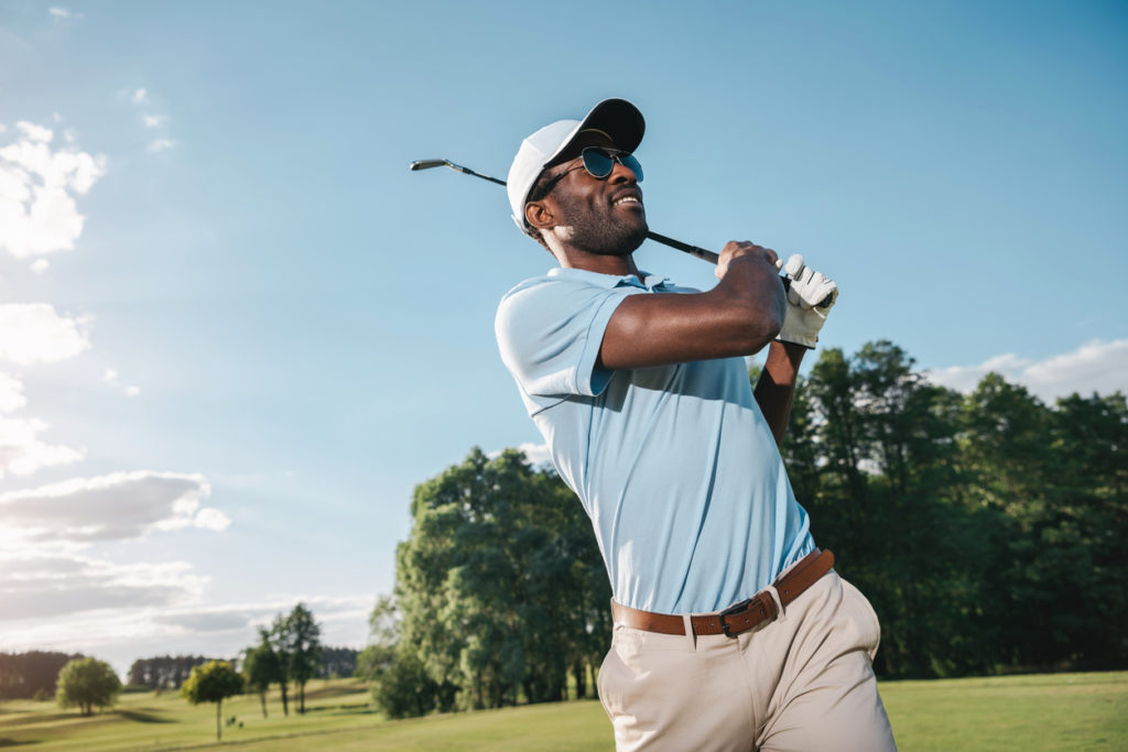 Smiling man in cap and sunglasses playing golf