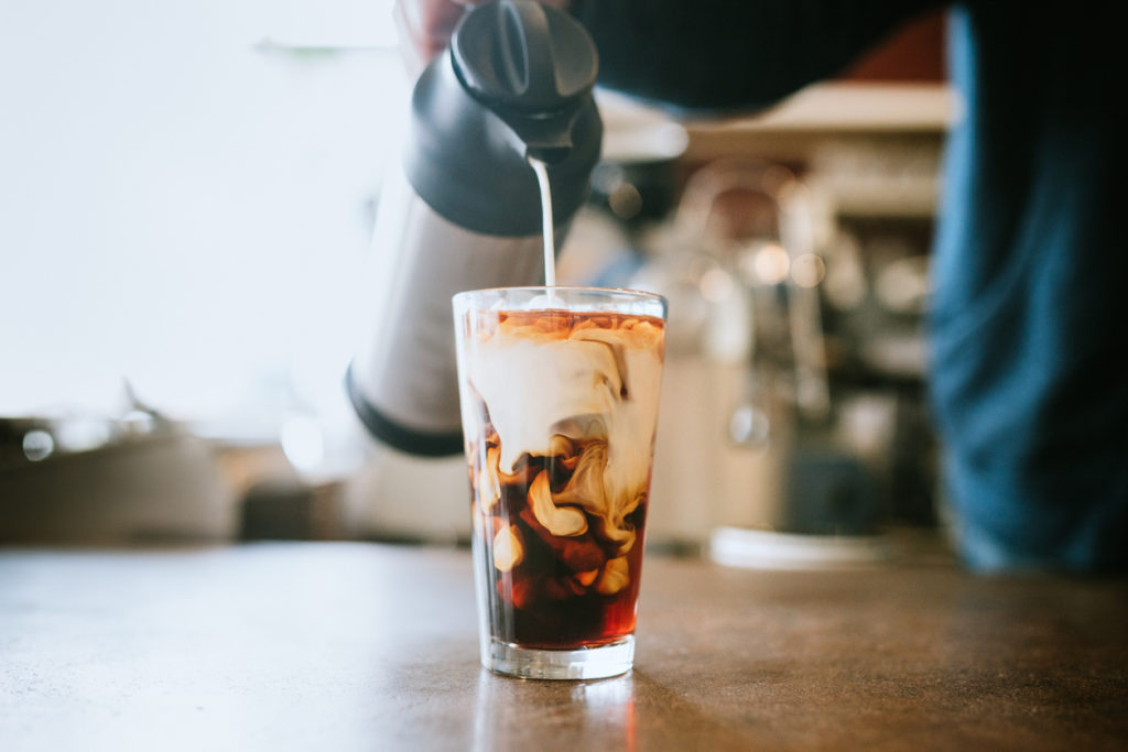 A man pours cold whole milk in to a glass of iced coffee