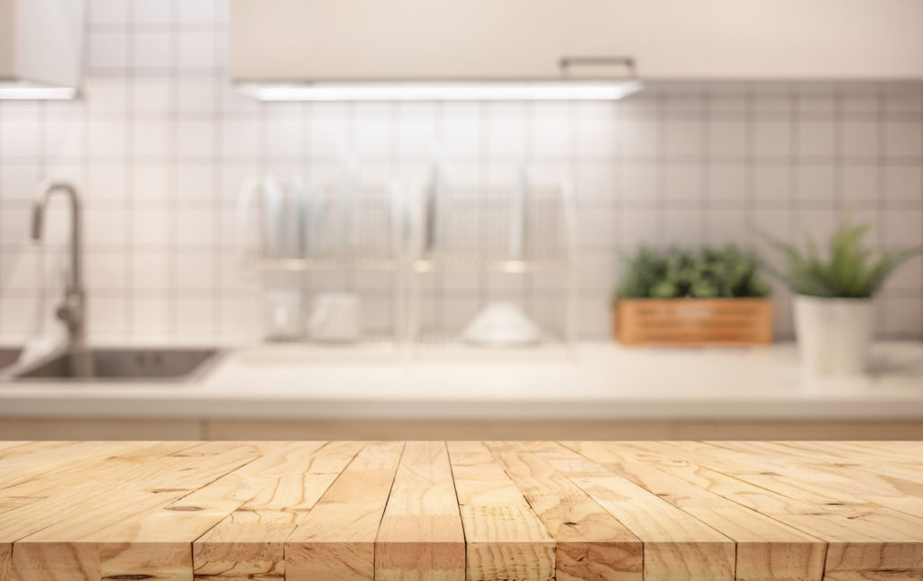 Wood table top on blur kitchen counter