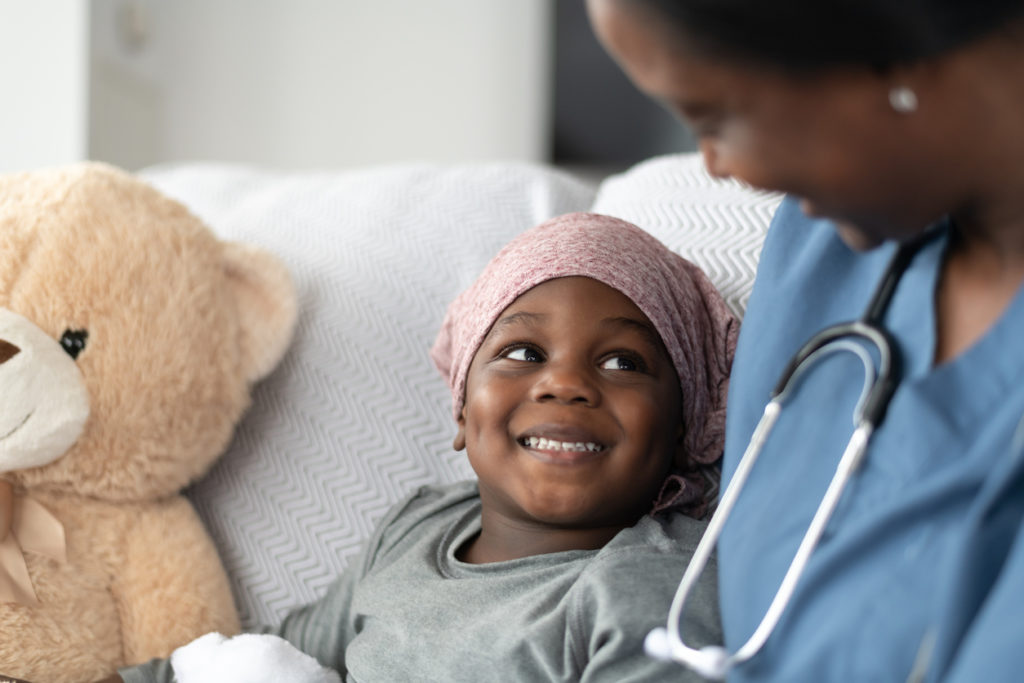 young boy with pediatric cancer smiling at doctor